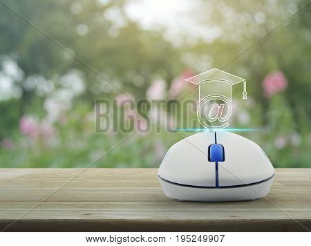 e-learning icon with wireless computer mouse on wooden table over blur pink flower and tree Study online concept