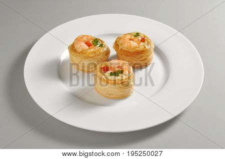 Round dish with vol au vent appetizer isolated on grey background