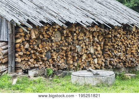 Chopped firewood stacked in a woodpile under a canopy