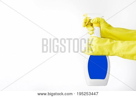 Hand in a rubber yellow glove holds  spray bottle of liquid detergent on a white background. cleaning