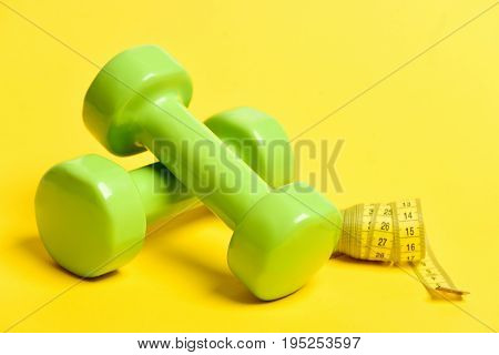 Green Lightweight Dumbbells And Rolled Tube Of Yellow Measuring Tape