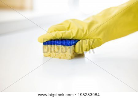 Female hand in a rubber yellow glove cleans the surface of the table
