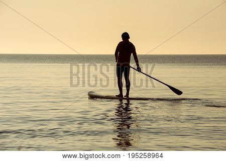 SUP silhouette of athletic man standing with a paddle on the surfboard at sunset stand up paddle boarding