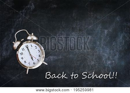 Dusty blank school chalkboard or blackboard with clock and back to school message. Room for copy space.