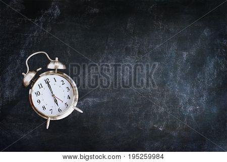 Dusty blank school chalkboard or blackboard with clock. Room for copy space.