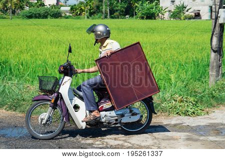 Hoi An - August 15, 2015: a Vietnamese man transporting a wooden table on a motorscooter.