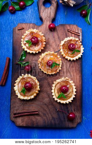 Apple Caramel Little Tarts On Wooden Board And Blue Rustic Background. French Tatin With Paradise Ap