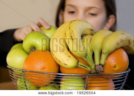 girl takes apple from fruit bowl