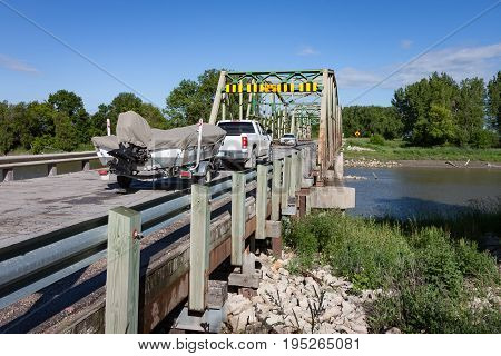 A Truck Pulling Boat on Trailer on River Bridge Meeting a Car