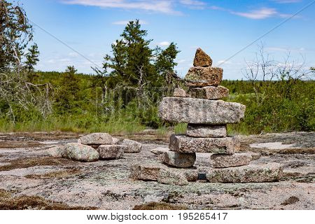 A large inukshuk stands on a broad rocky plain part of the Canadian Shield