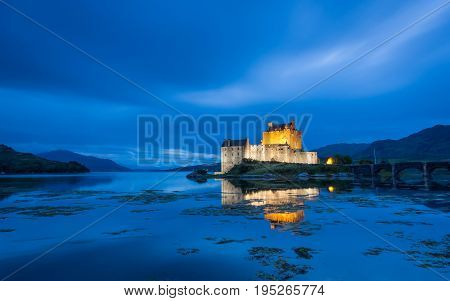 Illuminated Eilean Donan Castle in Scotland at dusk with blue clouds