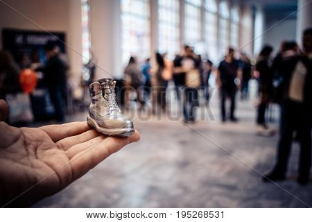 Object in the form of a boot printed on a 3d printer and covered with enamel on hand close-up. On the back of a blurry plan - people. Progressive modern additive technology. Copy spase