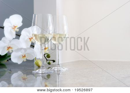 white wine in glasses on countertop - orchids in background - room for copy