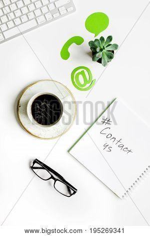 customer support service desktop with contact us signs on white office background top view