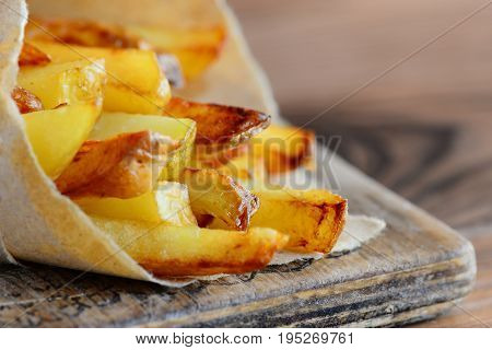 Homemade potato fries. Roasted golden potato fries in paper and wooden board. Closeup