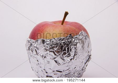 One ripe red apple beautiful wrapped in foil on a white background