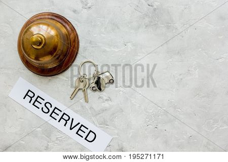 reception desk in hotel with ring and keys on gray stone background top view space for text
