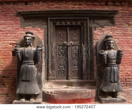 KATHMANDU, BHAKTAPUR, NEPAL. 30 September 2008: Entrance to a public Hindu temple. Two statues in the Taleju Chowk just inside the Golden gate in Bhaktapur.