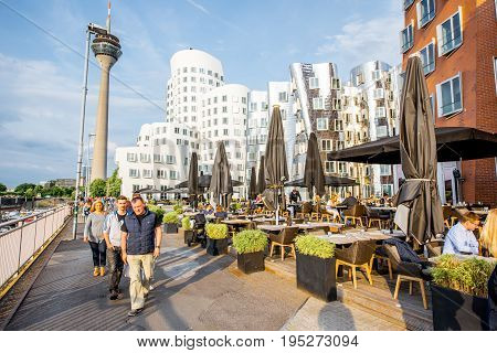 DUSSELDORF, GERMANY - July 04, 2017: Neuer Zollhof complex designed by Frank Gehry architects with crowded cafe on the waterfront of the Media Harbour in Dusseldorf