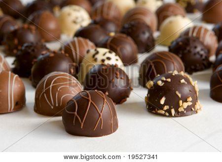 chocolate truffle background - focus on front truffle