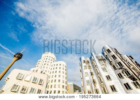 DUSSELDORF, GERMANY - July 04, 2017: Neuer Zollhof complex designed by Frank Gehry architects with television tower on the waterfront of the Media Harbour in Dusseldorf