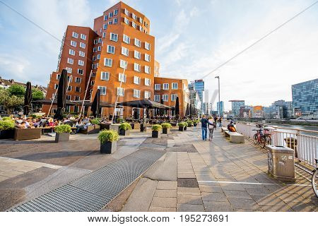 DUSSELDORF, GERMANY - July 04, 2017: Neuer Zollhof complex designed bey Frank Gehry architects with crowded cafe on the waterfront of the Media Harbour in Dusseldorf