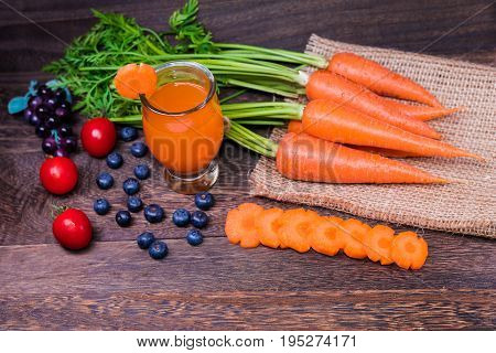 Healthy eating and dieting conceptfresh carrot and carrot juice or organic healthy juice in glass tomato and blueberries on a grey wooden table wall background