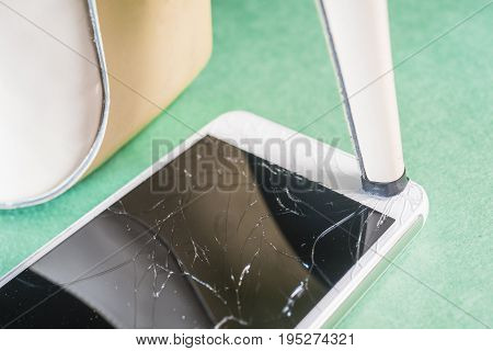 High-heeled shoes break the mobile phone on a light green background