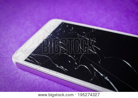 Crushed mobile phone on a lilac background