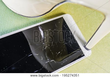 High heel crushing a mobile phone on a yellow green background