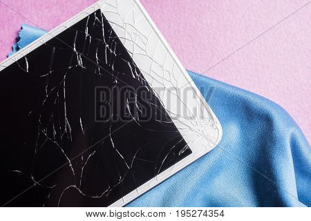 Broken mobile phone screen on a pink background