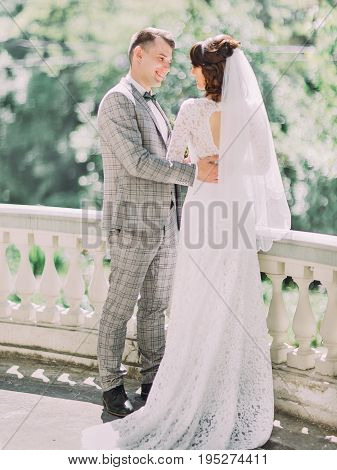 The lovely photo of the smiling newlyweds hugging on the balcony