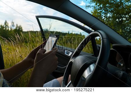 Motorist lost his way. The man is trying to find the way on the navigator in the mobile phone. Field in the background.