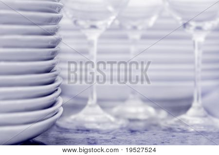 plates in foreground, wineglasses and more dishes in background - focus is on edge of plats