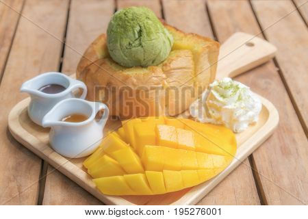 Honey toast green tea ice-cream with ripe barracuda mango and whipping cream in wooden plate on wooden table.