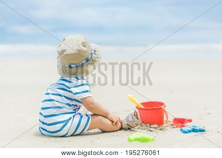 Asian 9 months baby boy playing on the sandy summer beach near the sea. Summer Travel Holiday concept.