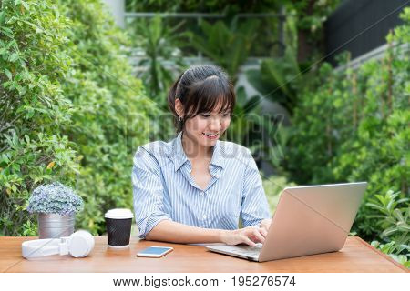 Asian woman in smiling face using laptop workplace in tree garden. Concept of Asian woman lifestyle.