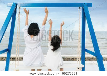Happy Asian family Mother with child having fun swinging near sea. Summer vacation travel and holiday family concept.