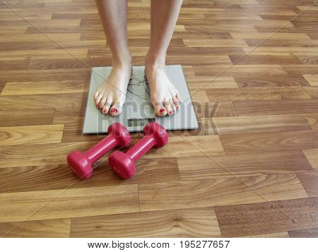 Female legs stand on the scales and two red dumbbells lie near on the floor. Two slender legs with a red pedicure gray electronic scales and two red dumbbells lie on the brown floor