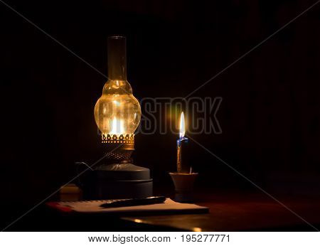 Kerosene lamp yellow flame and a candle light notebook with pen in a dark room
