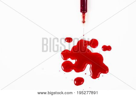 Drop of blood from needle syringe over white background.