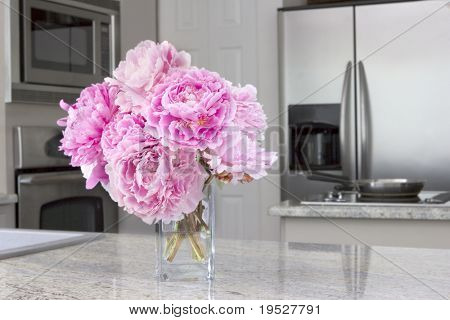 vase of pink peony flowers in modern grey kitchen