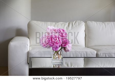 vase of pink peony flowers with white living room furniture