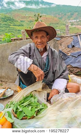 Lobesa Village Punakha Bhutan - September 11 2016: Unidentified smiling old man at weekly farmers market. Fresh fruits and vegetables for sale at the local market.