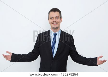 Successful male leader outstretching arms and looking at camera. Positive young businessman in suit shrugging shoulders as symbol uncertainty. Or he welcoming new clients. Modern businessman concept