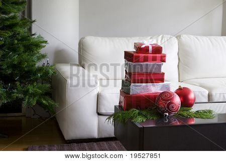 christmas presents and red ornaments on coffee table with xmas tree