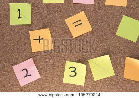 Multiple multi-coloured post it notes on a wooden background