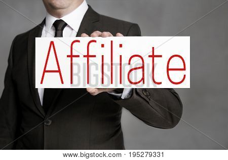 Affiliate signboard is held by businessman background