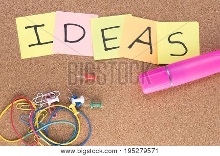Ideas written on post it notes with a pink highlighter and rubber bands, taken on a wooden background with copy space