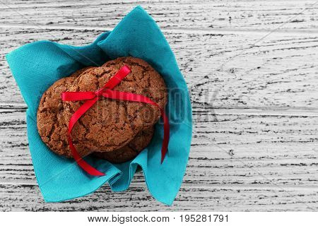 Chocolate chip cookies with red bow on white wood background